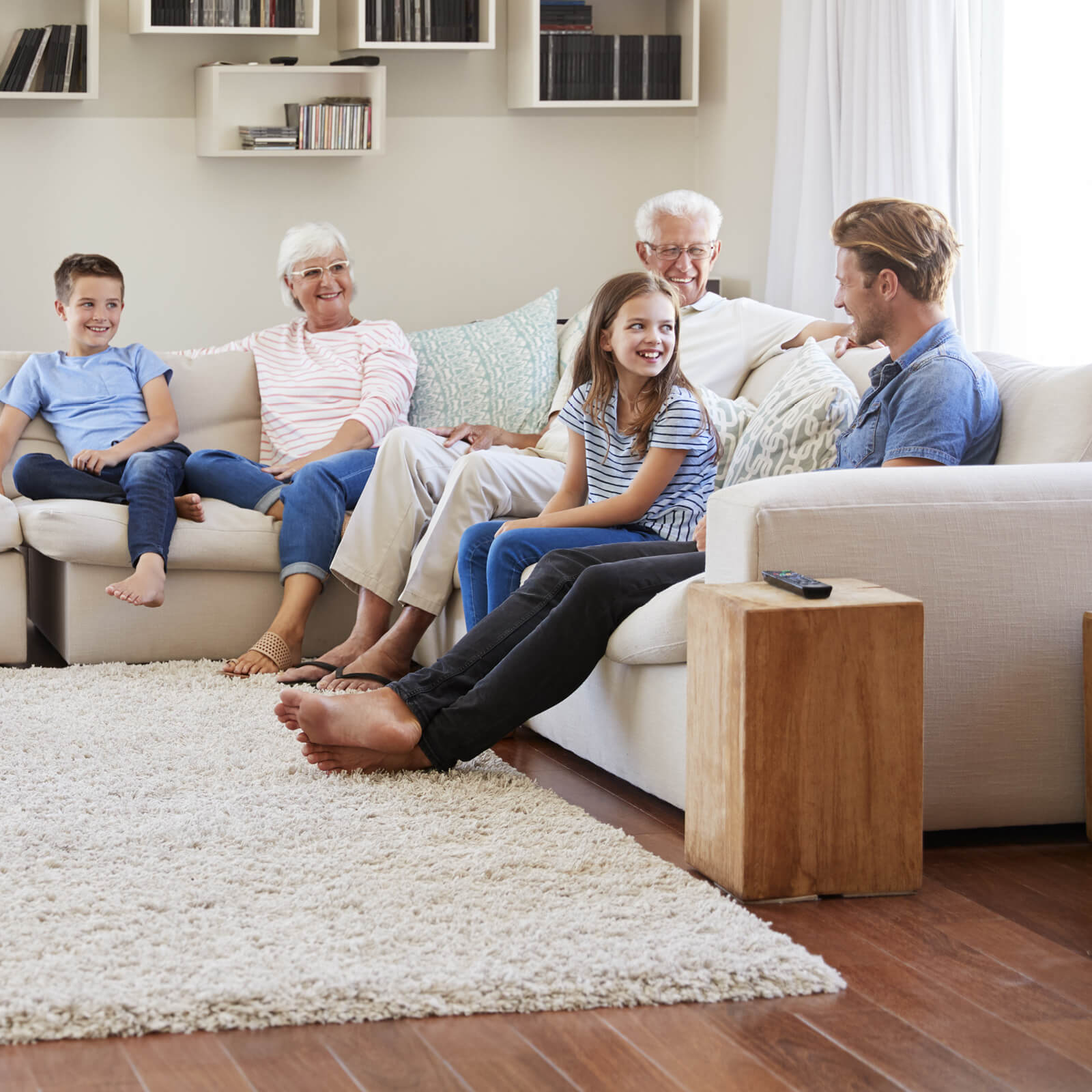 Family Sitting Around an Area Rug