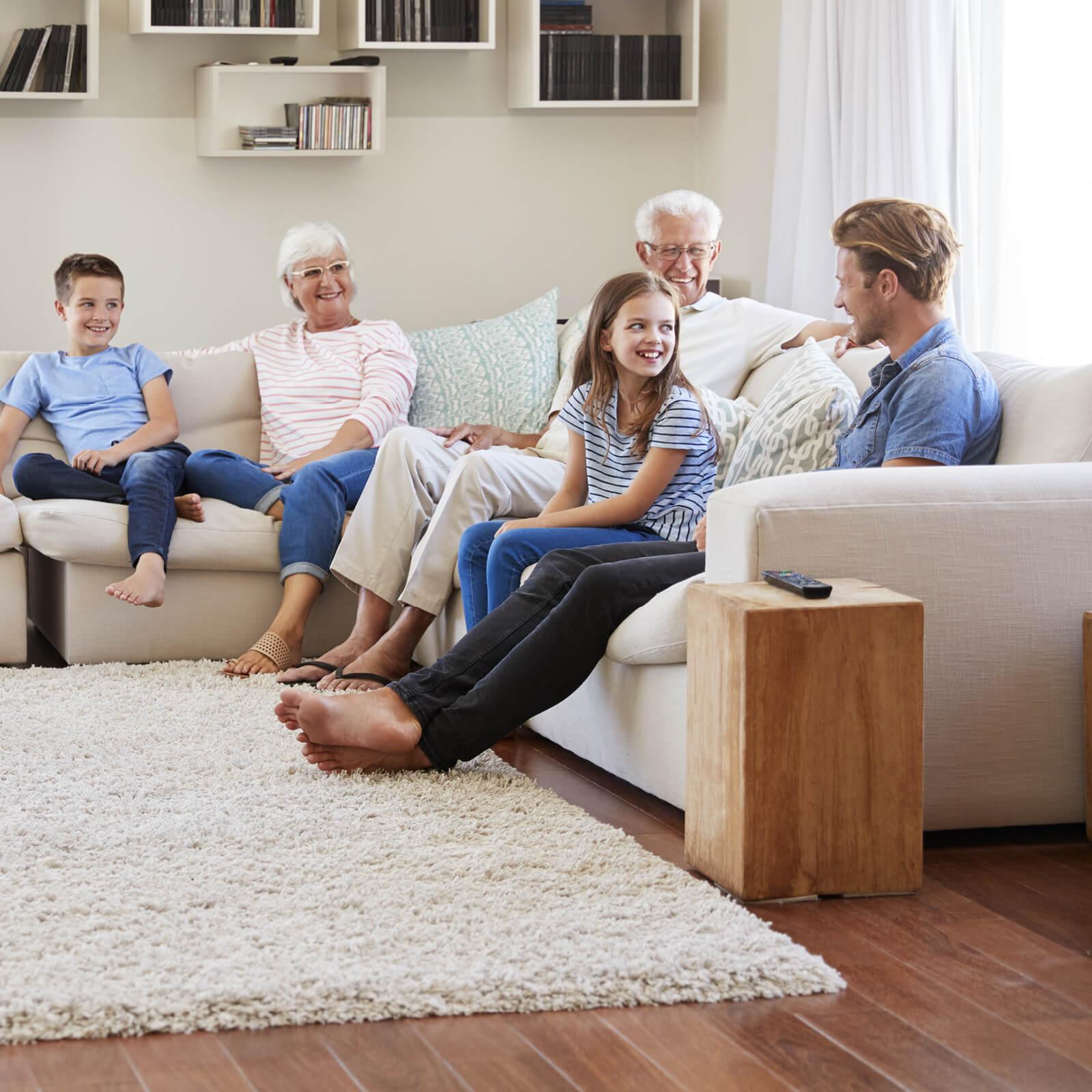 Family Sitting Around an Area Rug